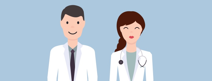 A male doctor in a white coat and a female doctor in a white coat with a stethoscope stand side by side smiling.