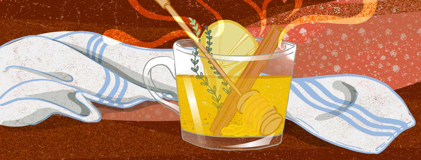 a hot toddy with a honey dipper, lemon and cinnamon
