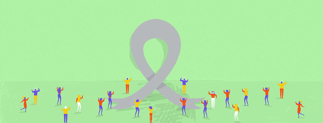 people surrounding a large awareness ribbon
