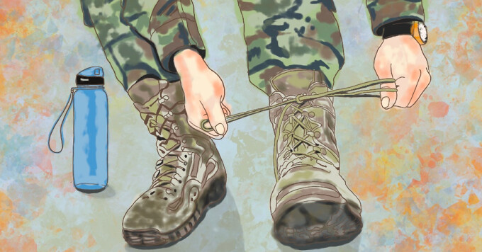 military soldier tying up a boot with an inhaler and water bottle next to them